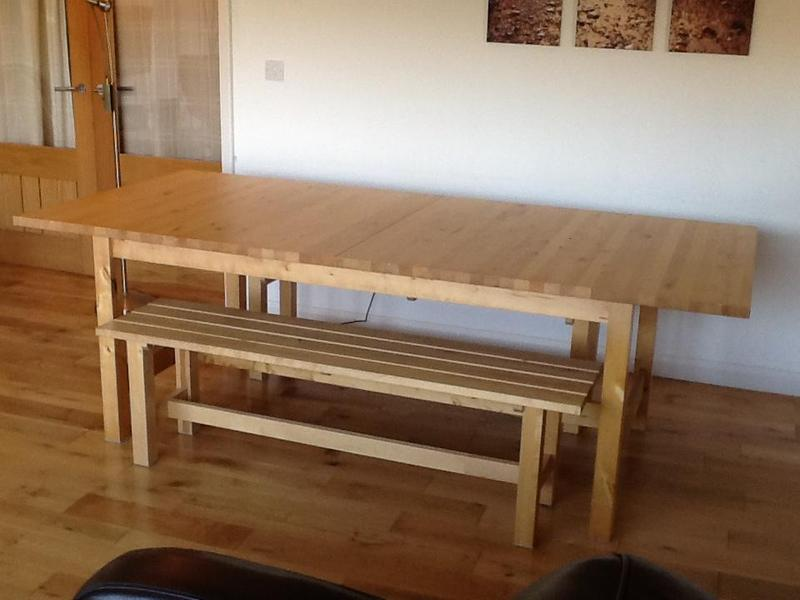massive ikea solid wood dining table with two benches in east cowes
